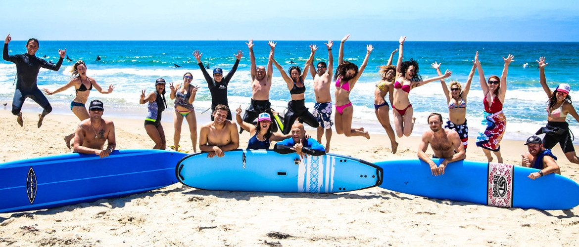 Surfing students jumping for joy after first lesson